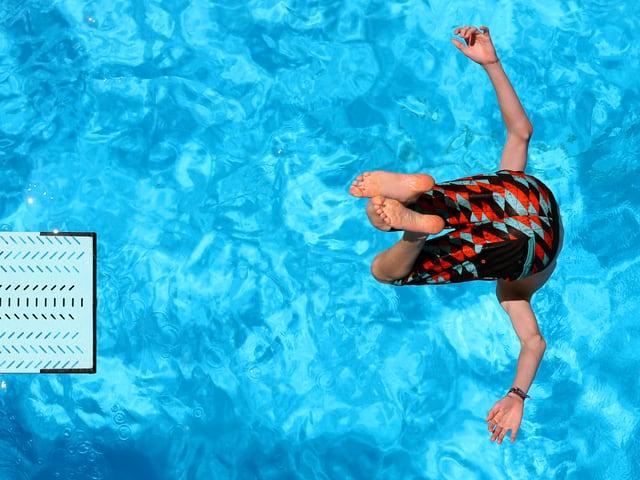 Ein Junge springt von einem Sprungbrett ins Wasser