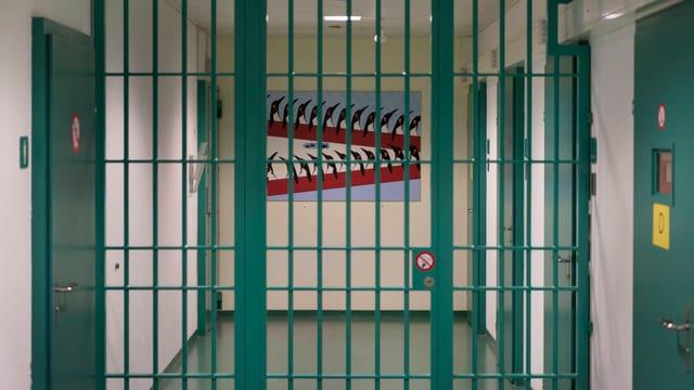 Gefängnisgang, den ein grünes Gitter zweiteilt, rechts und links gehen grüne Zellentüren ab