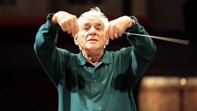 Älterer Mann mit grauen Haaren und dunkelgrünem Shirt dirigiert Orchester während einer Probe