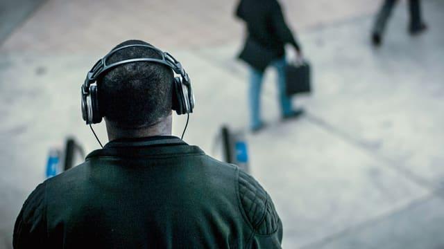 Ein Mann mit Kopfhörern von hinten.