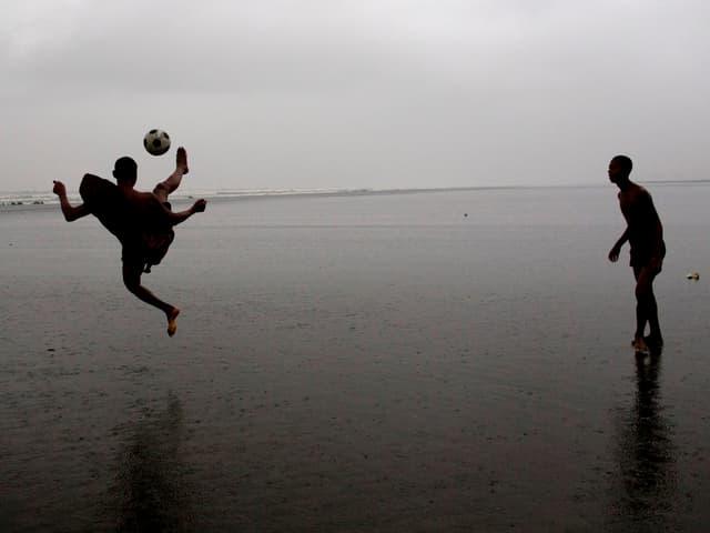 Zwei Männer spielen im Meer Fussball.