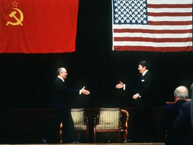 Michail Gorbatschow und Roland Reagan strecken einander die Hand zur Begrüssung hin.