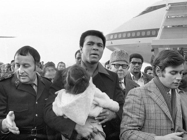 Muhammad Ali bei seiner Ankunft 1971 in Kloten mit seiner kleinen Tochter auf dem Arm.