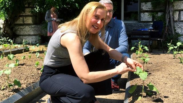 eine Frau kniet in der Erde und zeigt ein Loch im Blatt
