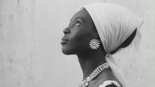Bild aus einem Schwarzweissfilm: Eine junge dunkelhäutige Frau mit Kopftuch