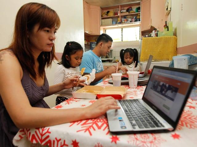 Die Philippinin Sheila Ortencio arbeitet in ihrer Küche als Online-Freelancerin, umgeben von ihren Kindern.