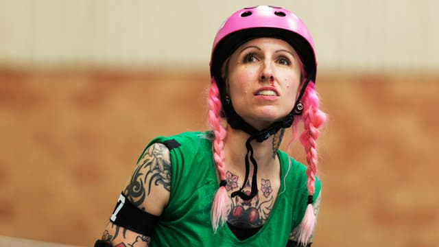 Frau mit rosa Helm und rosa gefärbten Haaren und vielen Tattoos.
