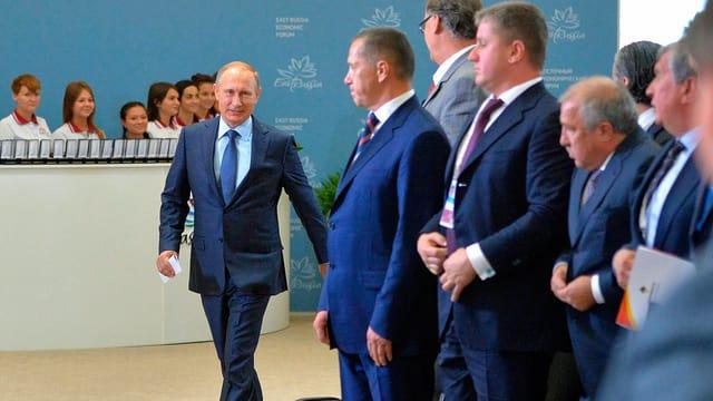 Putin läuft an mehreren Männern vorbei.