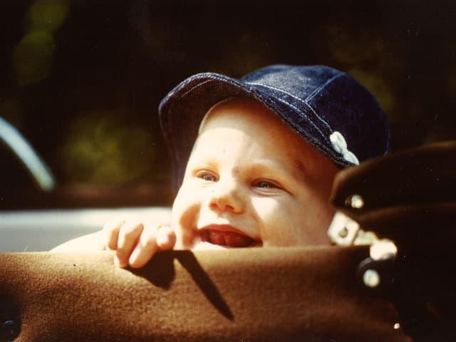 Ein Kleinkind mit blauem Sonnenhut blickt neugierig aus einem Kinderwagen.