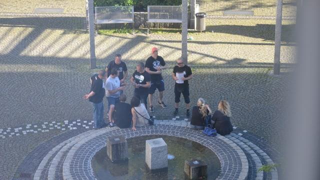 Zehn Menschen sitzen um einen modernen Brunnen.