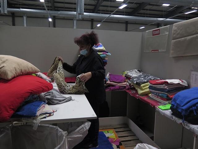 Eine Frau nimmt die gebrauchten Kleider auseinander und kontrolliert sie.