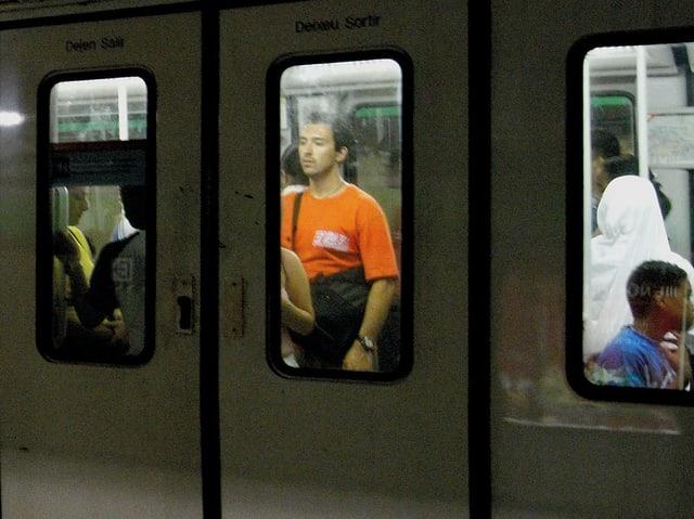 Ein junger, nordafrikanisch aussehender Mann in einem orangen T-Shirt steht in der U-Bahn, blickt durch das Fenster der geschlossenen Türen.