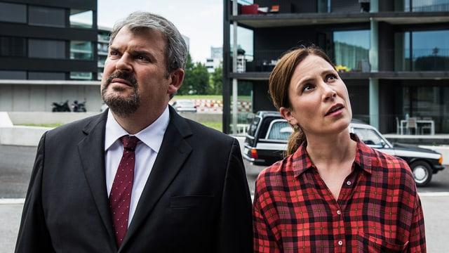 Filmszene: Mann und Frau Stehen nebeneinander. Er schaut nach links oben, sie nach rechts oben.