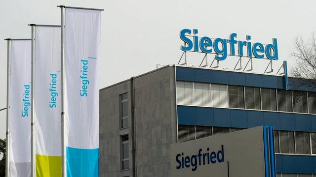 Ein Gebäude mit zwei Siegfried-Schriftzügen im Hintergrund. Vorne Siegfried-Fahnen.