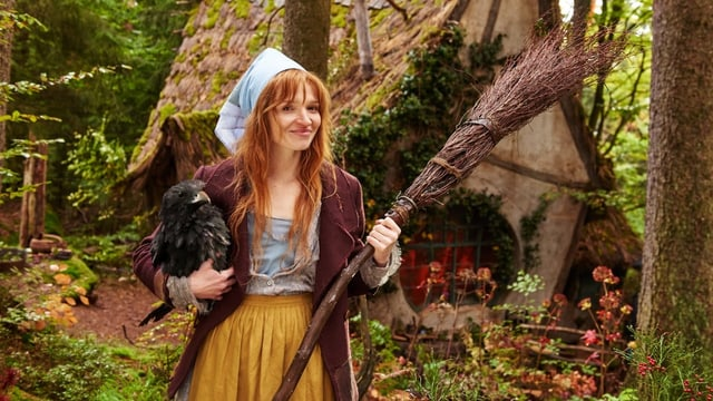 Die kleine Hexe posiert vor ihrer Hütte.