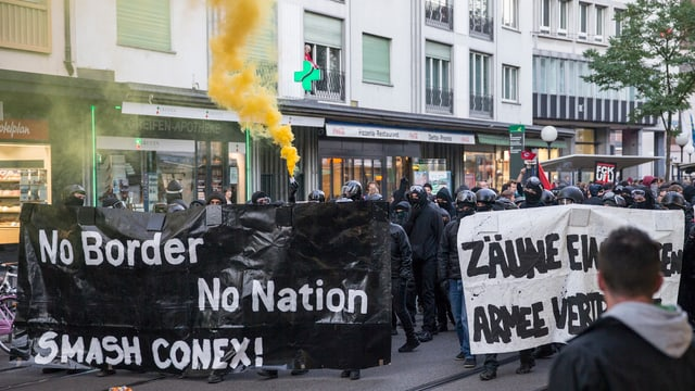 Schwarzvermummte Demonstranten halten ein schwarzes Transparent mit der Aufschirft: «No Border, No Nation. Smash Conex!»