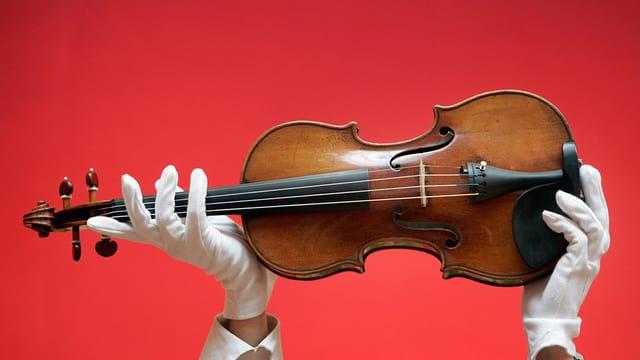 Hände in weissen Handschuhenhalten eine Geige in die Höhe.