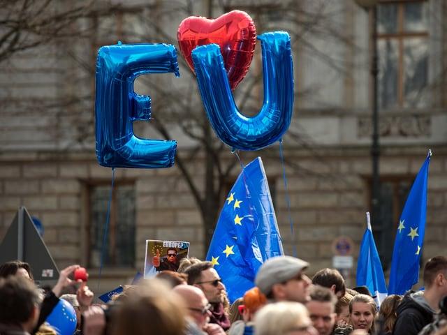 Demonstranten halten am in Berlin auf der Strasse Unter den Linden Luftballons hoch, die die Kürzel  «EU» bilden.