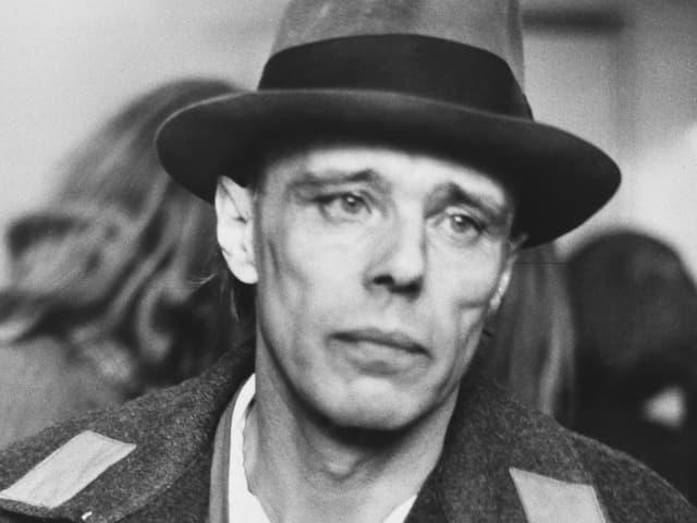 Beuys mit Hut, Mantel und Zigarette.