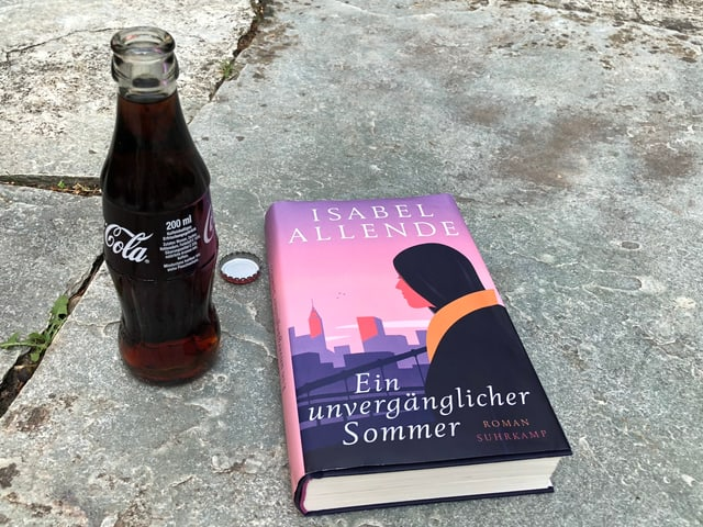 Der Roman «Ein unvergänglicher Sommer» von Isabel Allende liegt auf einem Spaghetti-Liegestuhl, ein Eis-Zitronen-Limonade steht daneben