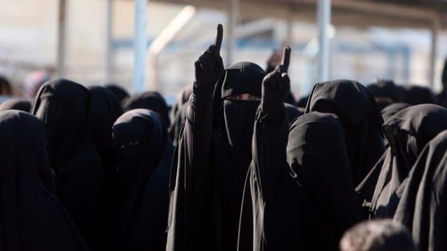Frauen schwarz verhüllt, einige strecken den Zeigfinger in die Höhe.