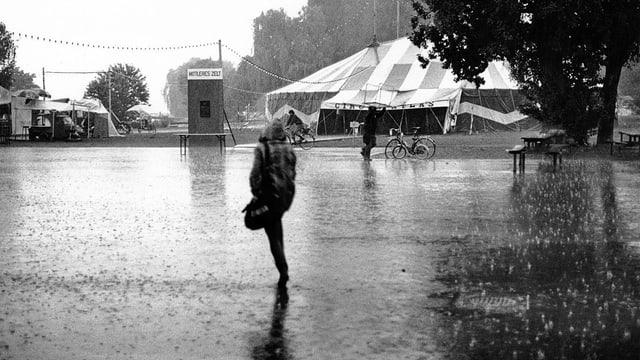 Eine Frau rennt im Regenschutz durch die Nässe.