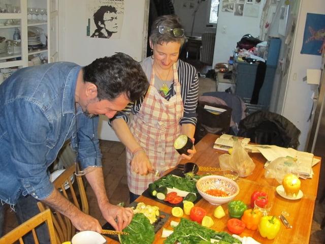 Khalid Ahmed und Séverine Vitali stehen am Küchetisch und bereiten das Gemüse vor