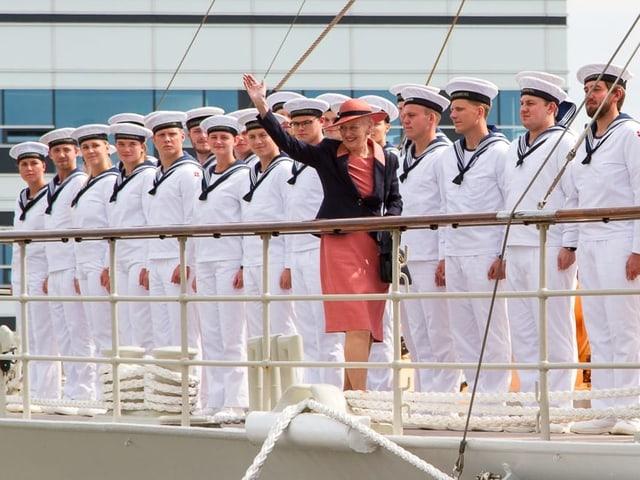 Königin Margrethe winkt von einem Schiff runter. Hinter ihr stehen Matrosen stramm.