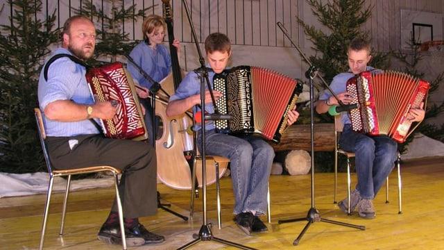 Drei Akkordeonspieler und eine Kontrabassistin auf einer Konzertbühne.