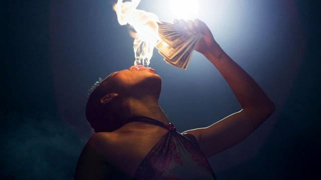 Ein schwarze Frau Frau spuckt Feuer, in der Hand hält Sie ein Bündel Dollar-Scheine.