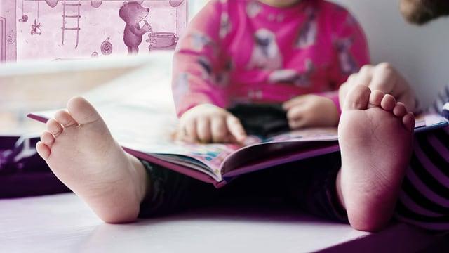 Kind schaut ein Bilderbuch an. Im Hintergrund eine Illustration eines Bären, der kocht.
