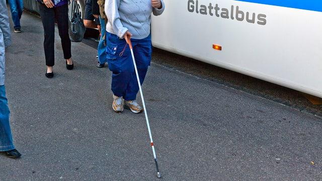 Eine blinde Frau auf einem Bahnsteig.
