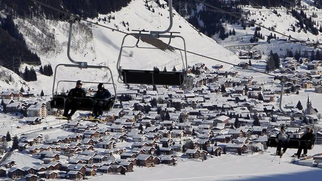 Blick auf das winterliche Sedrun, Sessellift im Vordergrund.