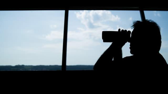 Mann mit Fernglas vor grossem Fenster.