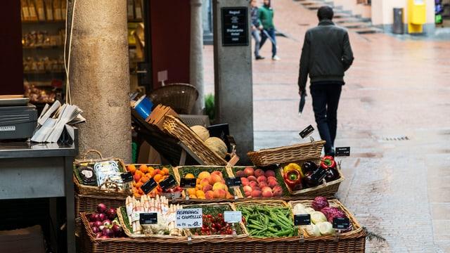 Marktstand in der Leventina mit Obst und Gemüse in Körben.