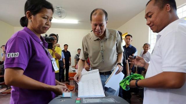 il president actual Benigno Aquino pren encunter la glista d'elecziun en in local d'eleger.