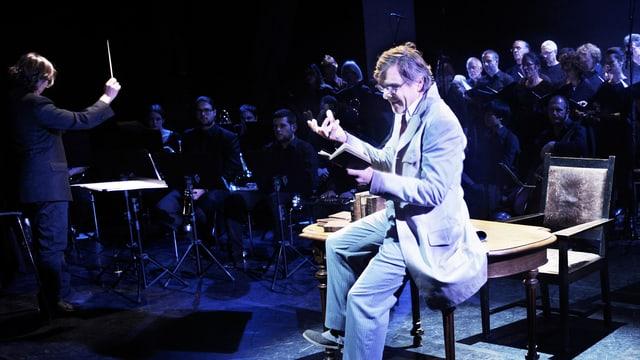 Ein Mann sitzt auf einem Stuhl. Hinter ihm ist ein Orchester.