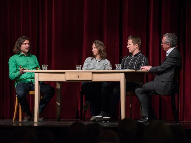 Diskutierende Leute an einem Tisch auf einer Bühne.