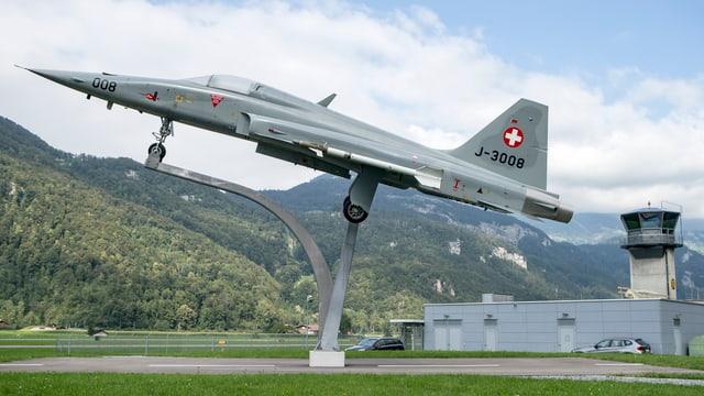 Ein Kampfjet auf einer Halterung, im Hintergrund der Tower, dahinter die Berge.
