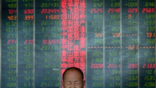 Mann mit geschlossenen Augen vor einer Tafel mit Aktienkursen.