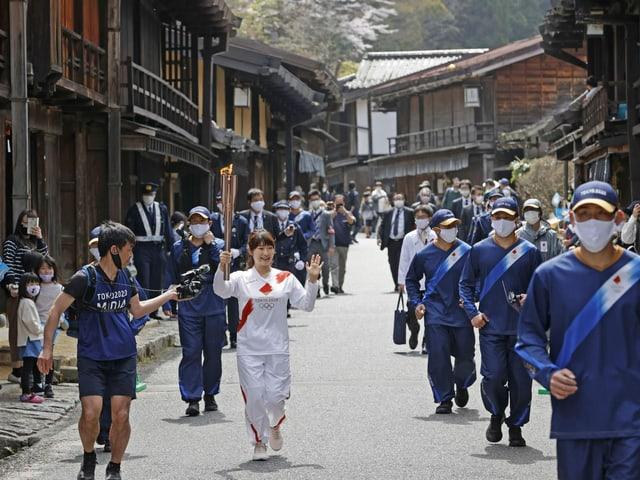 Hier wird das olympische Feuer durch die Stadt Nagiso getragen.
