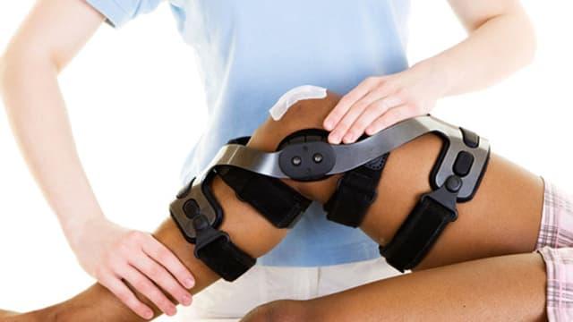 Physiotherapeutin kümmert sich um verletztes Sportlerknie.