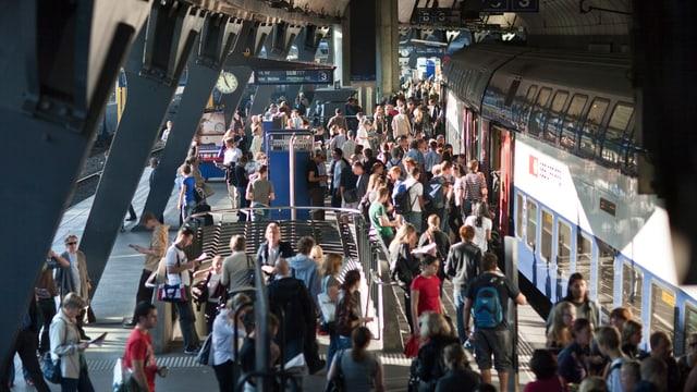 Vollbesetzter Bahnsteig neben einem Zug