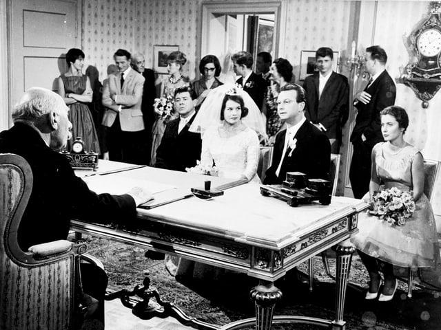 Ein Standesbeamter traut ein Brautpaar. Im Hintergrund ist die Hochzeitsgesellschaft zu erkennen.