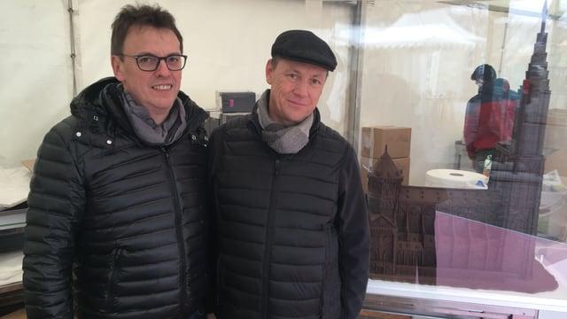Zwei Männer mit schwarzen Jacken und Schokoladenhaus