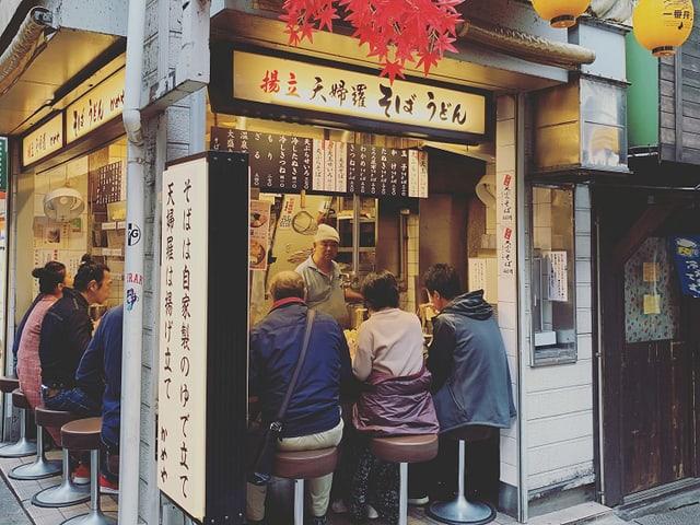 Diverse Leute essen in einem japanischen Nudel-Restaurant schnell eine Schlale Nudeln.