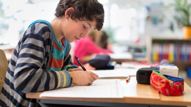 Schüler schreibt am Pult in einem Schulzimmer.