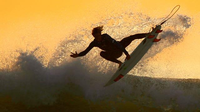 Ein Surfer in der Luft über einer Welle in der Abendsonne.