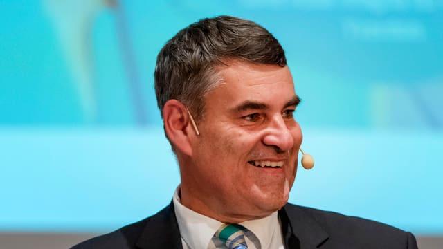 Christian Amsler - ein grosser Mann mit braun-meliertem Haar, und einem Mikrofon vor blauem Hintergrund.