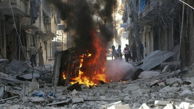 Destrucziun totala ad Aleppo suenter in'attatga ord l'aria. In auto stat en flommas amez las ruinas.